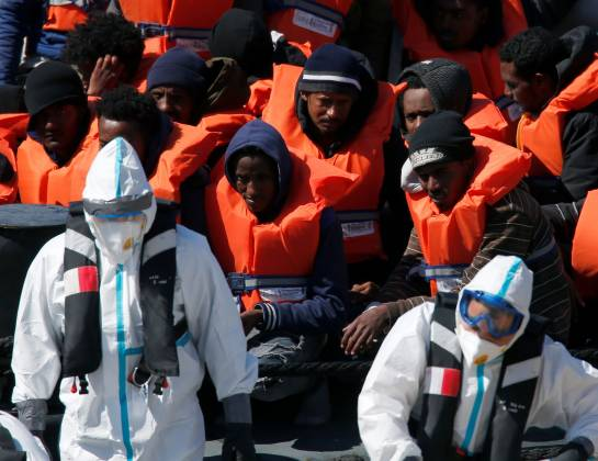 Armed Forces of Malta soldiers in protective clothing against possible coronavirus infection stand near rescued migrants on a military ship as it arrives in Senglea