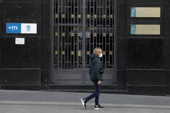 A woman, wearing a protective mask, walks in the empty Alacal street during partial lockdown, as part of a 15-day state of emergency to combat the coronavirus outbreak in Madrid