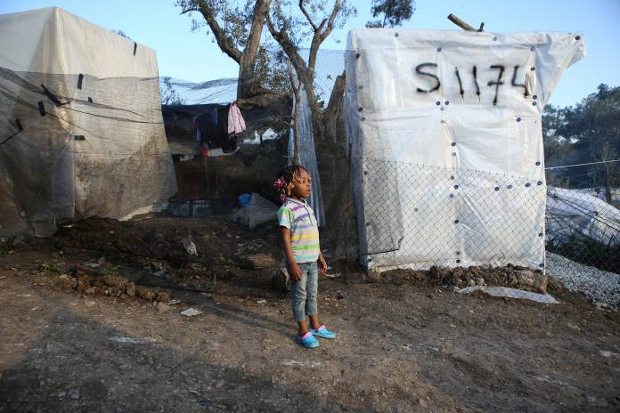 FILE PHOTO: A child stand next to tents, at a makeshift camp for refugees and migrants next to the Moria camp, on the island of Lesbos