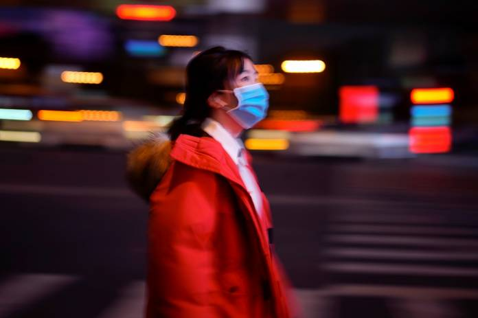 A woman wearing a protective face mask is seen on a crossroad following the outbreak of coronavirus disease (COVID-19), in downtown Shanghai