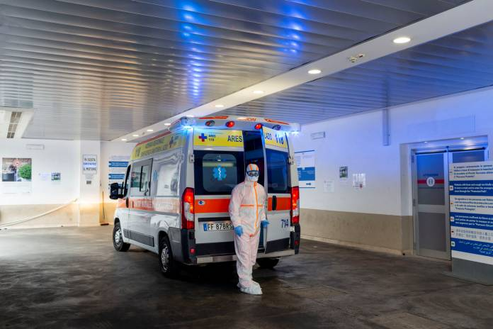 A medical worker in a protective suit stands by an ambulance in the emergency room of the Gemelli Hospital, where coronavirus patients are looked after, in Rome