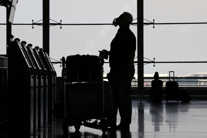 A man wearing protective mask is seen in silhouette as he looks at an information board at Kuala Lumpur International Airport, after Malaysia's government closed its borders due to the spread of the coronavirus disease (COVID-19), in Sepang