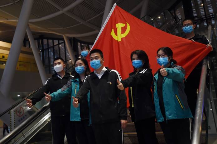 Medical workers from outside Wuhan pose for pictures with a Chinese Communist Party flag at the Wuhan Railway Station before leaving the epicentre of the novel coronavirus disease outbreak