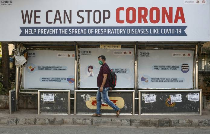 A man wearing a protective mask walks past a bus stop displaying preventive measures against the coronavirus in Mumbai