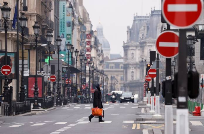 A man wearing a protective face mask crosses the deserted Rue de Rivoli in Paris