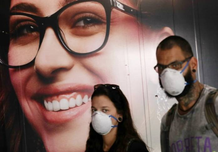 People wear protective face masks at international arrivals area at Guarulhos International Airport, amid coronavirus fears, in Guarulhos