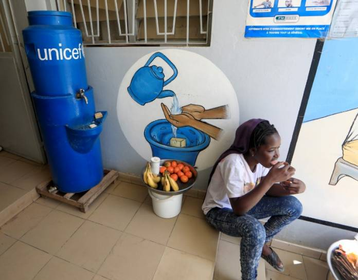 A girl eats as she sits next to a handwashing station, while she sells fruits at the entrance of a medical center in Pikine, on the outskirts of Dakar