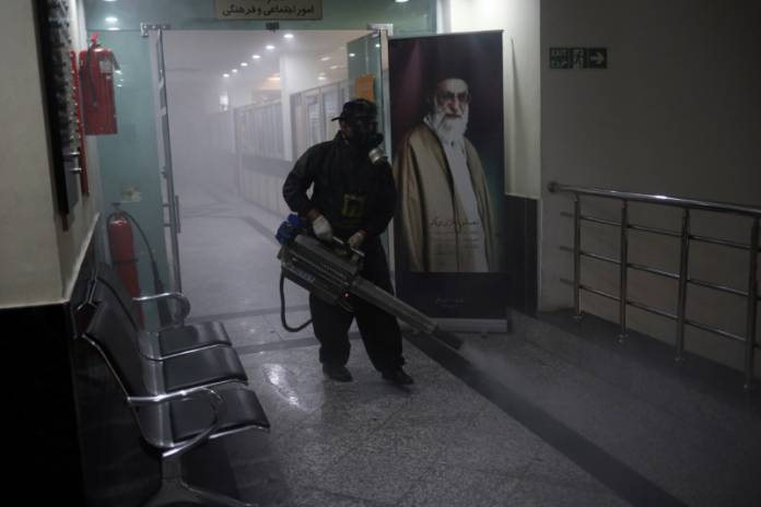A member of firefighters wears a protective face mask, amid fear of coronavirus disease (COVID-19), as he disinfects a municipality building, ahead of the Iranian New Year Nowruz, March 20, in Tehran