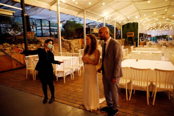 Israeli couple Roni Ben-Ari and Yonatan Meushar, look on as they get married at Ein Hemed Forest Wedding Venue, in Ein Hemed, Israel