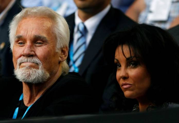 FILE PHOTO: Rogers and his wife Wanda Miller watch the match between Nadal of Spain and Cilic of Croatia at the Australian Open tennis tournament in Melbourne