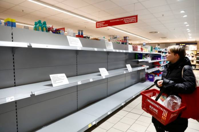 FILE PHOTO: A woman looks at an empty shelf with a sign announcing the rationing of toilet paper at a Rewe grocery store in Potsdam