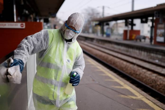 FILE PHOTO: A worker cleans the train station with disinfectant to slow the rate of the coronavirus disease in Suresnes