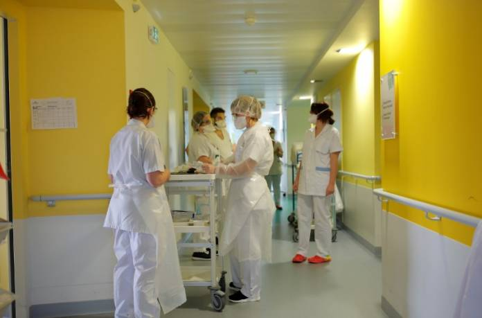 FILE PHOTO: Medical workers wearing protective masks and suits are seen at the pulmonology unit at the hospital in Vannes