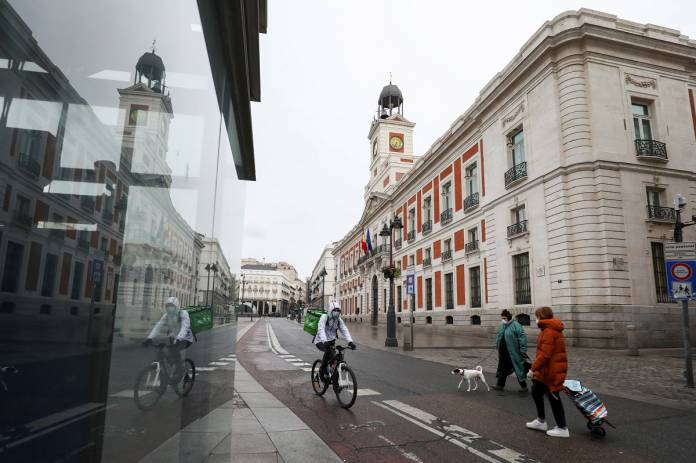 People wearing protective face masks are seen in an almost empty Puerta del Sol in Madrid