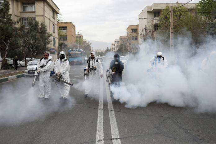 Members of firefighters wear protective face masks, amid fear of coronavirus disease, as they disinfect the streets, ahead of the Iranian New Year Nowruz, March 20, in Tehran