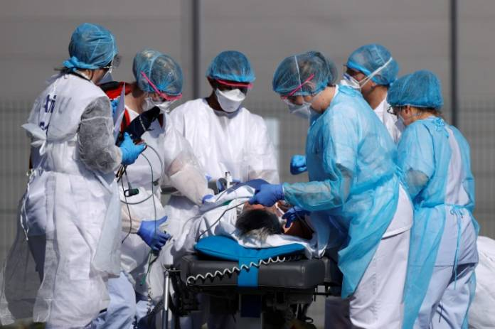 French rescue team wearing protective suits carry a patient on a stretcher from Mulhouse hospital