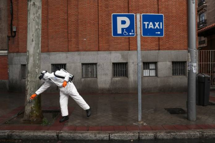 A municipal worker in protective gear disinfects a street during the coronavirus disease (COVID-19) outbreak in Madrid