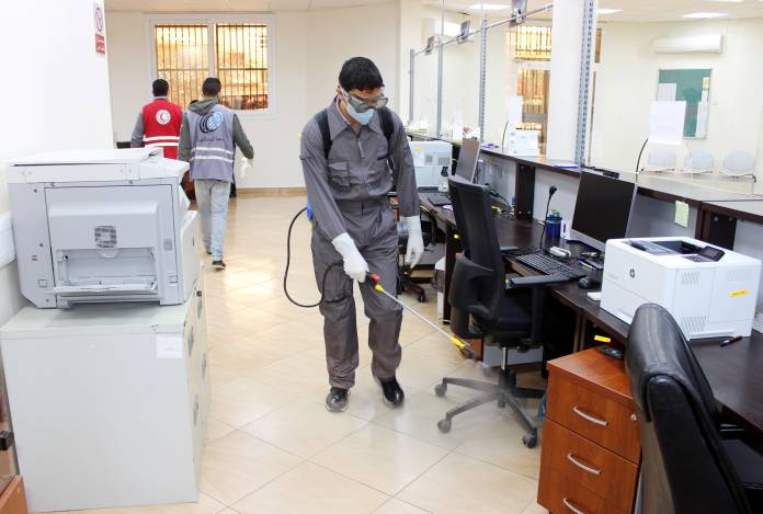 Members of Red Crescent spray disinfectants at government offices in Misrata