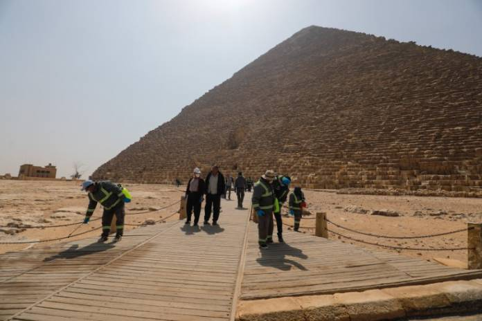Members of the medical team spray disinfectant as a precautionary move amid concerns over the coronavirus disease (COVID-19) outbreak at the Great Pyramids, Giza, on the outskirts of Cairo