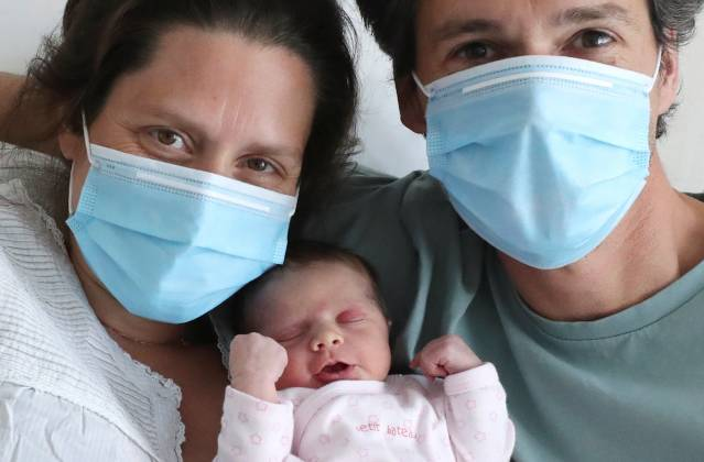 Amandine, who tested positive for the coronavirus disease (COVID-19) just before giving birth, and Francois, wearing protective face masks, are pictured with their newborn daughter Mahaut at the maternity at CHIREC Delta Hospital in Brussels