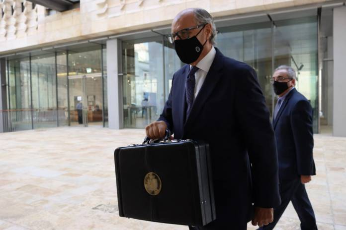 Finance Minister Edward Scicluna walks in with budget 2021