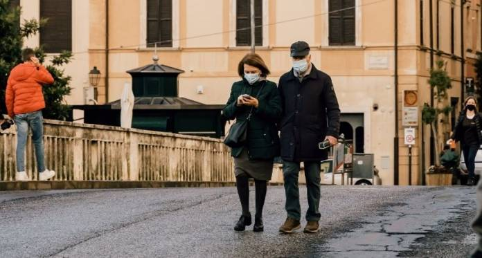 A-middle-aged-Italian-couple-wearing-face-masks-stroll-along-the-main-street-in-the-town-of-Rieti-Italy-Gabriella-Clare-Marino-coronavirus