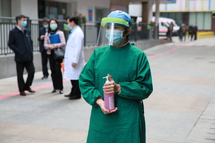 WHO-China joint mission on COVID-19: a woman dispenses hand sanitizer at the Guangzhou Women and Children's Health Medical Center in Guangzhou, Guangdong Province on 20 February 2020.