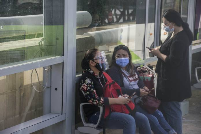 people-wearing-masks-while-waiting-for-the-bus