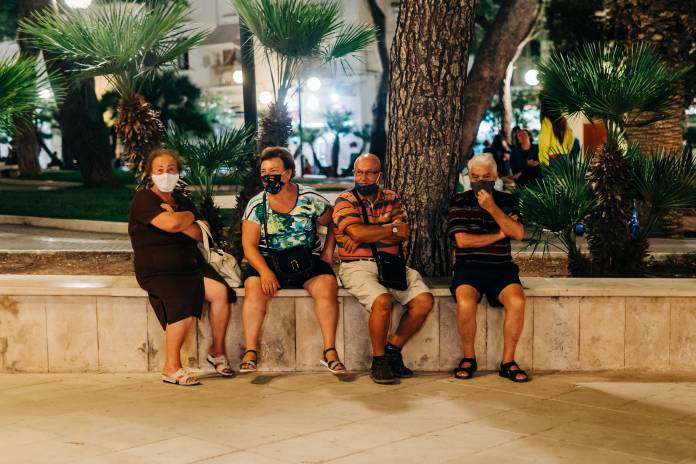 Two elderly couples wearing face masks sit people watching in a square in Puglia, Italy