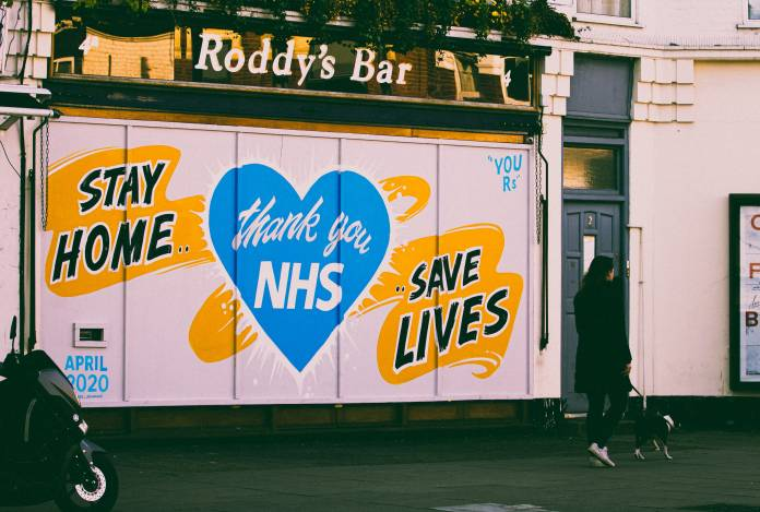 A woman walks past a street mural, during the lockdown in London 2020.