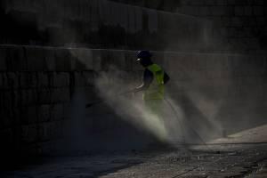 man-sprays-water-on-wall-in-breakwater-valletta