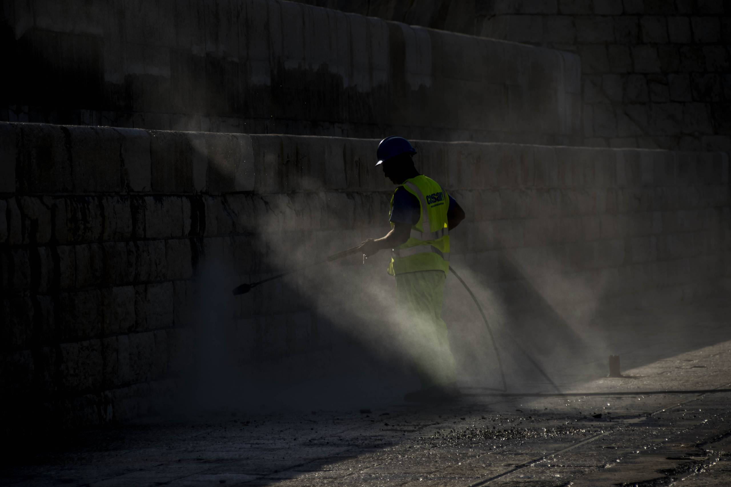 man-sprays-water-on-wall-in-breakwater-valletta