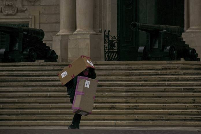 person-wrapped-in-boxes-to-avoid-getting-wet-from-rain